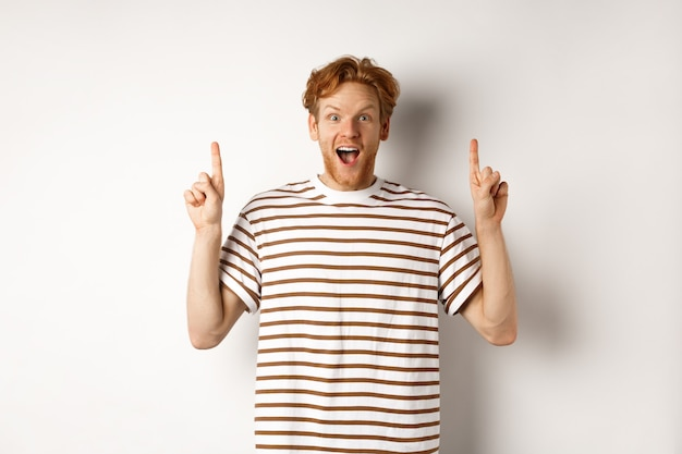 Amazed and excited redhead man checking out promotion, pointing fingers up and showing logo, staring at camera, standing over white background.