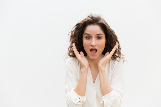 Amazed excited woman gasping, keeping hands at open mouth