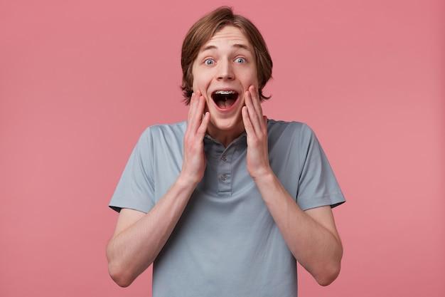 Il giovane ragazzo eccitato stupito che si tocca il viso non può credere alla sua fortuna, con i capelli lunghi ben pettinati e le parentesi graffe sui denti indossa la maglietta polo gridando e si sente felice sorpreso isolato su un muro rosa