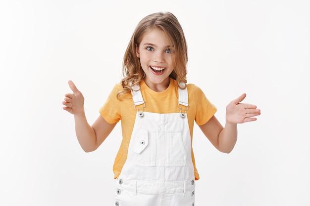 Пораженная очарованная симпатичная белокурая девушка объясняет размер продукта, взволнованно улыбается, демонстрирует длину руками, обсуждает большие или большие вещи, счастливая улыбка, встает у белой стены, представляет огромный объект
