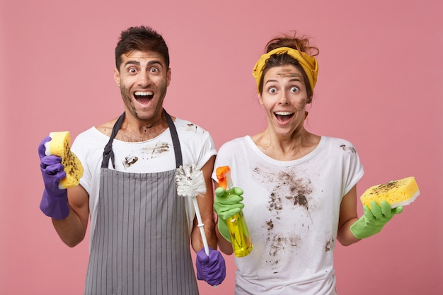 汚れた服と顔をした驚きの女性と男性は、非常に迅速に仕事を終えるために嬉しいことに驚いています。陽気な女性がスポンジを保持し、スプレーと彼女の夫をブラシとスポンジで洗う