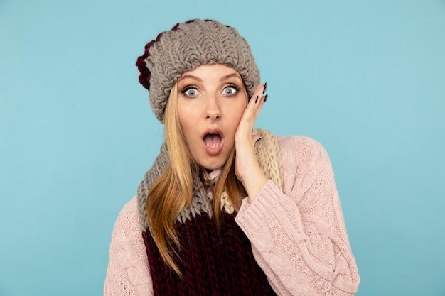 Пораженная женщина в зимней шапке, шарфе и свитере.