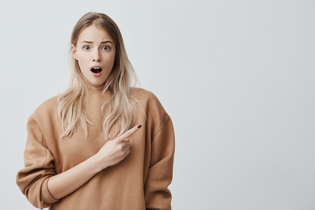 Amazed female model with straight long blonde hair, wearing beige clothes, looking with bugged eyes and widely opened mouth, pointing with forefinger at copy space