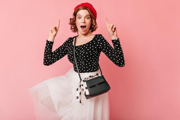 Пораженная французская девушка, указывая пальцами. студия выстрел удивленной молодой женщины в берете, изолированном на розовом фоне.