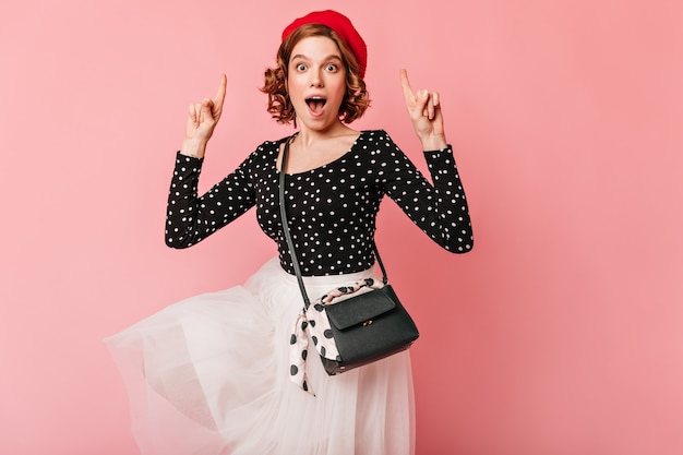 Amazed french girl pointing with fingers. studio shot of surprised young woman in beret isolated on pink background.