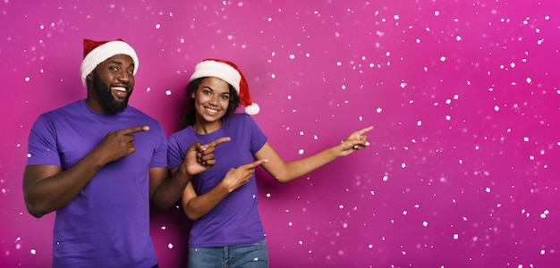Amazed friends surprised by the arrival of christmas. purple background