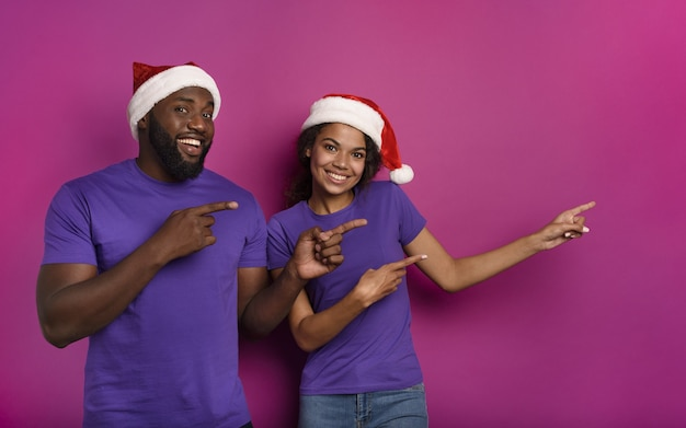 Amazed friends surprised by the arrival of christmas with hat. purple background