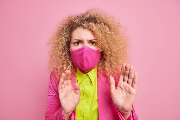 놀란 겁에 질린 여인이 손바닥을 들고 불안해 보이는 모습을 보이며 코로나 바이러스에 감염 될까 두려워 보호 마스크를 착용하고 분홍색 벽 위에 절연 된 밝고 화려한 옷을 입습니다. 바이러스 확산 중 무료 사진