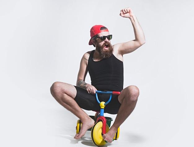 Пораженный забавный велосипедист, возбужденный человек на красочной велосипедной игрушке в кепке от солнцезащитных очков, катающийся на детском трехколесном велосипеде