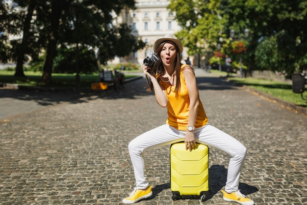 Amazed funny traveler tourist woman in casual clothes, hat sitting on suitcase with retro vintage photo camera outdoor. girl traveling abroad to travel on weekends getaway. tourism journey lifestyle.