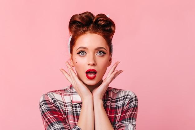 체크 무늬 셔츠에 포즈 놀된 생강 여자. 핑크 공간에 고립 충격 된 예쁜 여자의 전면 모습.
