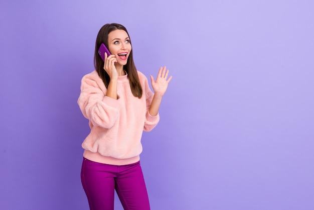驚いた女の子は紫色の背景で携帯電話の会話をしています
