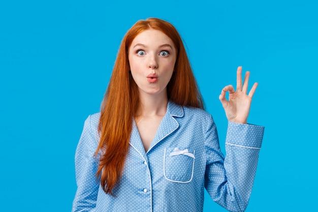 Удивленная девушка слышит о замечательном новом продукте. заинтересованная и удивленная рыжеволосая женщина в пижаме, складывая губы, говорит: «ого, изумленно уставилась и показала хороший жест»