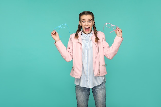 Пораженная девушка в повседневном или хипстерском стиле, прическа косичка, стоит, держит голубые и розовые очки и смотрит в камеру с удивленным лицом, съемка в закрытой студии, изолированная на синем или зеленом фоне