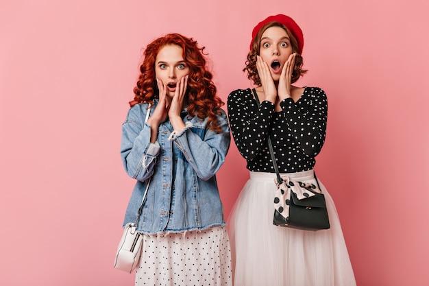 Пораженная девушка в джинсовой куртке позирует с другом. две привлекательные женщины, выражающие удивленные эмоции на розовом фоне.