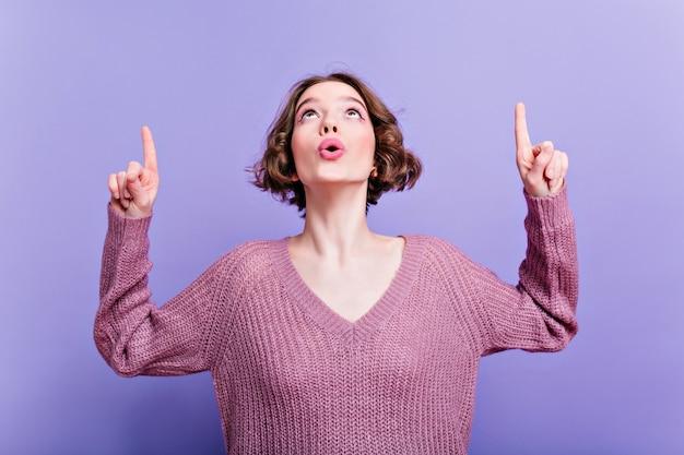 トレンディなニットセーターで見上げて指を指している驚いた女の子。紫色のウールの服を着た好奇心旺盛な女性は、何か面白いものを見ました。