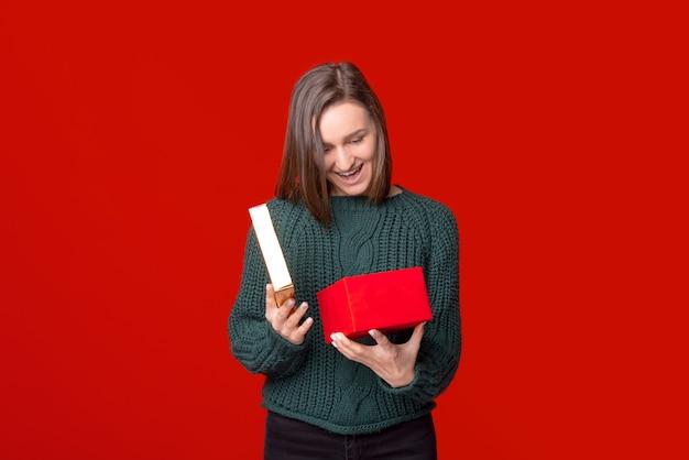 놀란 소녀는 선물 상자를 열고 빨간색 배경 위에 내부를 찾고 있습니다.