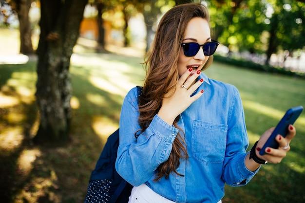 Пораженная девушка слушает онлайн музыку и смотрит медиаконтент на открытом воздухе в парке
