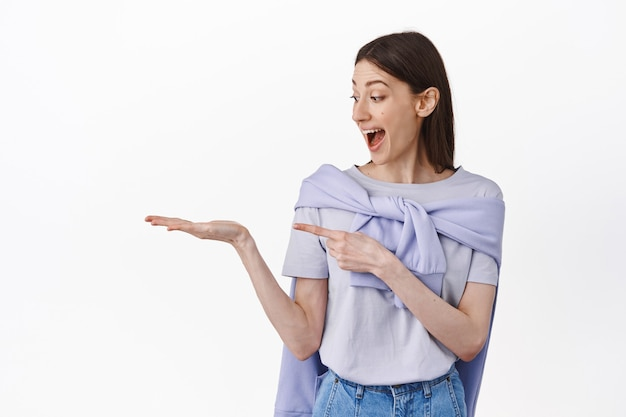 Ragazza stupita guarda il suo palmo aperto e indica un oggetto vuoto, mostrando un prodotto promozionale, in piedi eccitato contro il muro bianco