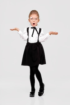 Amazed girl in a school uniform and round glasses spread her arms to the sides indignantly