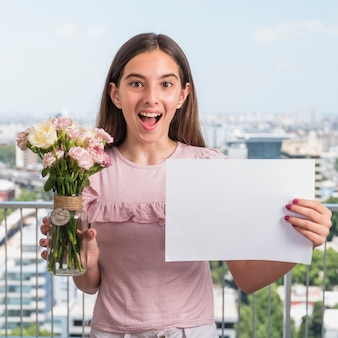 Amazed girl standing with flowers and paper