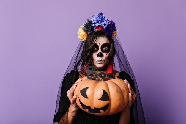 Amazed girl with halloween makeup holding painted pumpkin. portrait of dark-haired brunette in black outfit.