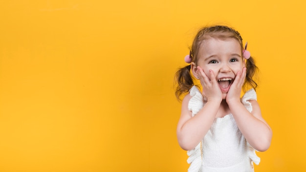 Amazed girl on yellow background
