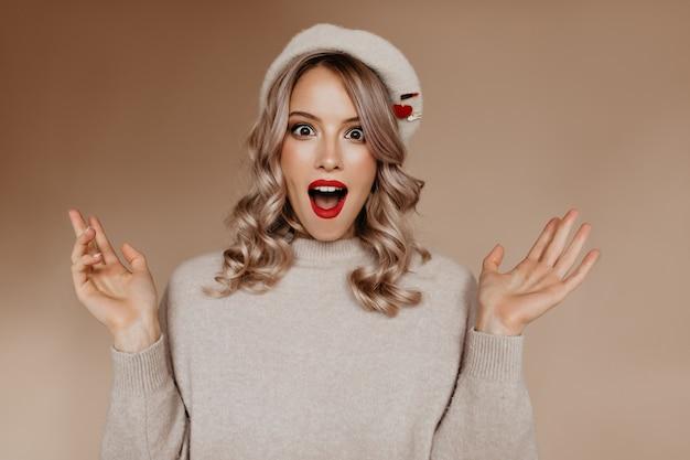 スタジオに立っている茶色のベレー帽で驚いたハンサムなフランス人女性