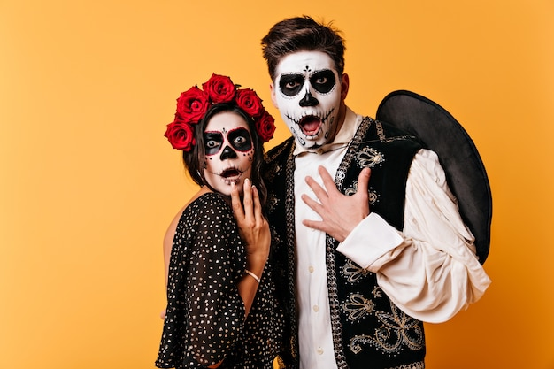 Amazed guy and girl with painted faces for halloween look in fright. shot of couple in national mexican costumes on isolated wall.