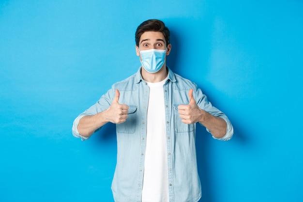 青い壁に立って、親指を立てて、プロモーションのオファーを推奨している医療マスクの驚いた男