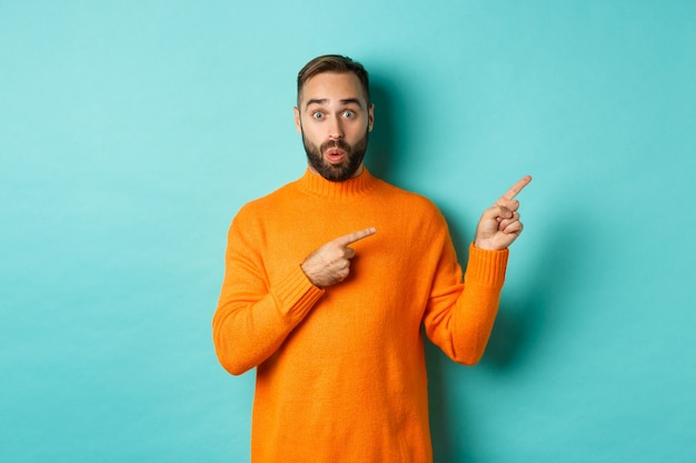 Amazed guy showing advertisement, pointing fingers right at banner, standing against turquoise background.
