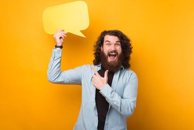 Пораженный бородатый красавец с длинными вьющимися волосами указывает на желтый речевой пузырь