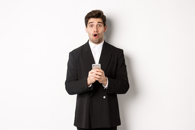 クールなプロモーションのオファーに反応し、携帯電話を持って、白い背景に立っている黒いスーツを着た驚いたハンサムな男