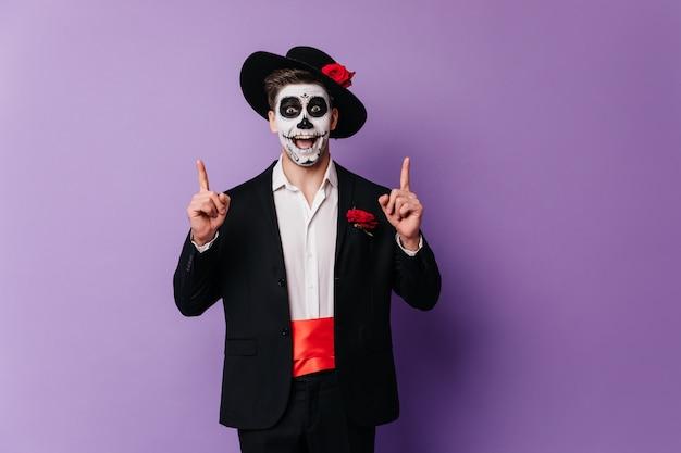 パーティーで身も凍るようなメキシコの服装で驚いたハンサムな男。ゾンビの衣装で感情的な男のハロウィーンの写真。