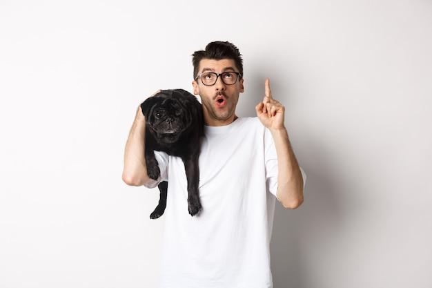 Amazed handsome man in glasses, holding cute black pug dog on shoulder, pointing finger up at promo logo, standing over white.
