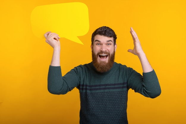 Amazed handsome man with beard holding yellow speech bubble