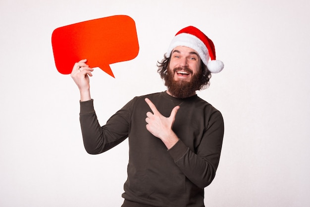 Amazed handsome man with beard pointing at empty speech bubble and wearing santa claus hat