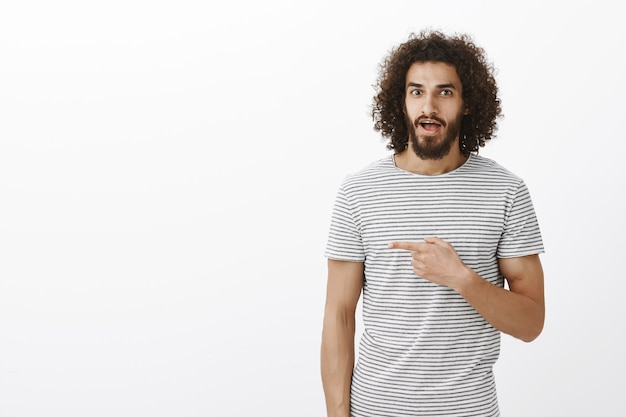 Amazed handsome musculine guy with beard and curly hair in trendy striped t-shirt, pointing right