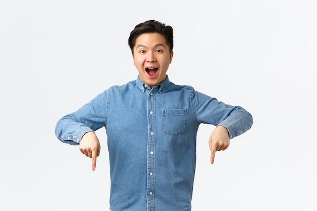 Ragazzo asiatico felice e stupito che fa un annuncio enorme, racconta grandi notizie fantastiche, punta il dito verso il basso sul banner. l'uomo che mostra pubblicità con espressione soddisfatta, consiglia compagnia.