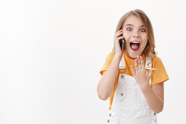 Stupito felice allegro ragazzino, eccitata ragazza bionda eccitata urla affascinata e gioiosa, ascolta ottime notizie tramite telefono cellulare, tieni lo smartphone vicino all'orecchio, apri la bocca meravigliata e compiaciuta