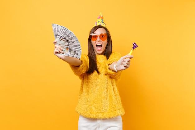 Пораженная счастливая молодая женщина в шляпе дня рождения очков оранжевого сердца с играющей трубой, держащей пачку долларов наличными деньгами, празднуя изолированные на желтом фоне. люди искренние эмоции, образ жизни.
