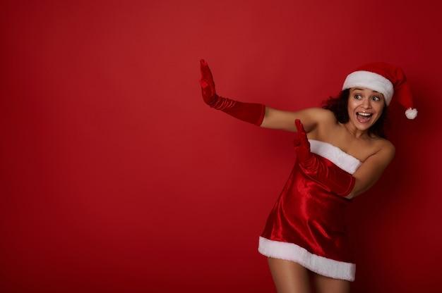 산타 옷을 입은 놀란 히스패닉계 여성은 빨간색 배경에 복사 공간을 들고 멀리 몸을 기댄다. 인간의 감정으로 크리스마스와 새해 광고를 위한 개념적 스튜디오 촬영