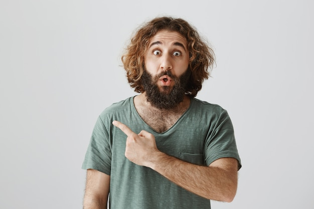 Amazed and impressed middle-eastern bearded man pointing finger left, saying wow
