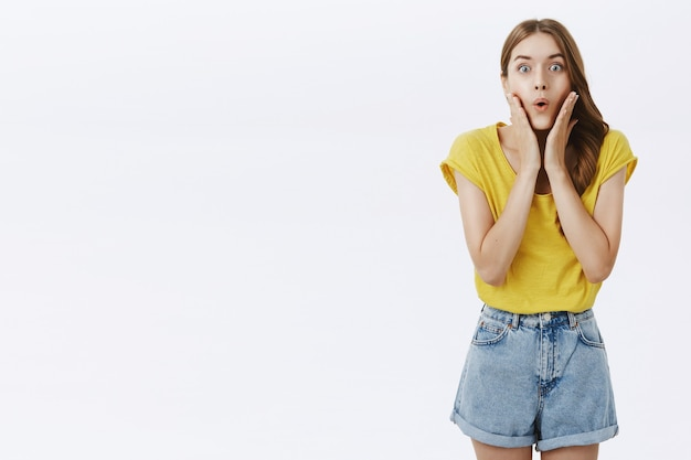 Amazed interested charming adult woman in yellow t-shirt and shorts folding lips holding palms on cheeks from curiosity and excitement