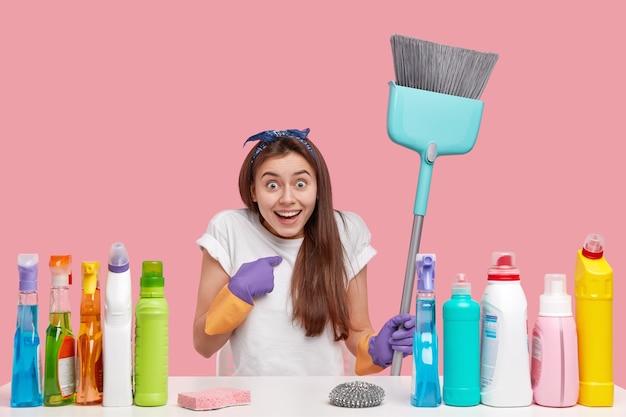La giovane donna gioiosa stupita indica se stessa, lavora nel servizio di pulizia, tiene in mano la scopa, si siede alla scrivania con detersivi e deodorante