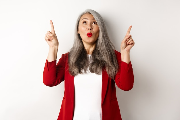 Amazed korean businesswoman with grey hair, wearing red blazer at work, pointing fingers up and looking surprised, standing over white background.