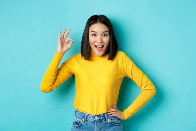 Пораженная корейская девушка показывает нормальный жест и улыбается в камеру, одобряет и рекомендует специальное предложение, стоя на синем фоне.