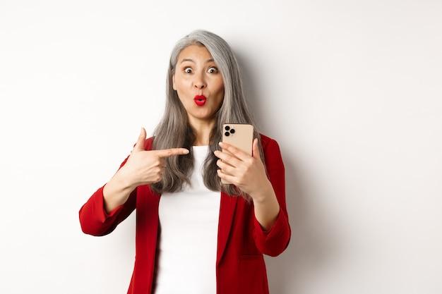 카메라, 흰색 배경에서 호기심을 찾고 휴대 전화에서 손가락을 가리키는 빨간 재킷에 놀란 된 한국 아가씨.