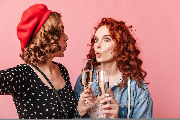 シャンパンを飲んで驚いた女性。ピンクの背景にワイングラスを持って驚いた女の子のスタジオショット。
