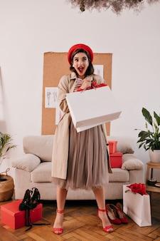 빨간 베레모와 베이지 색 트렌치에 놀란 여자는 흰색 쇼핑백과 함께 포즈를 취합니다. 밝은 모자와 가을 코트에 놀란 된 여자는 아파트에서 카메라를 살펴 봅니다.